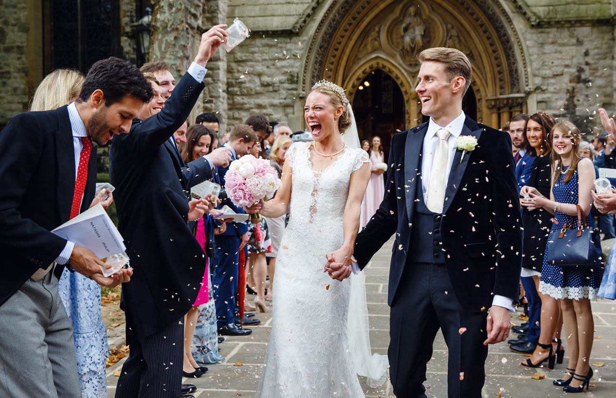 A couple walk through confetti outside St Mary Abbots church in Kensington, London