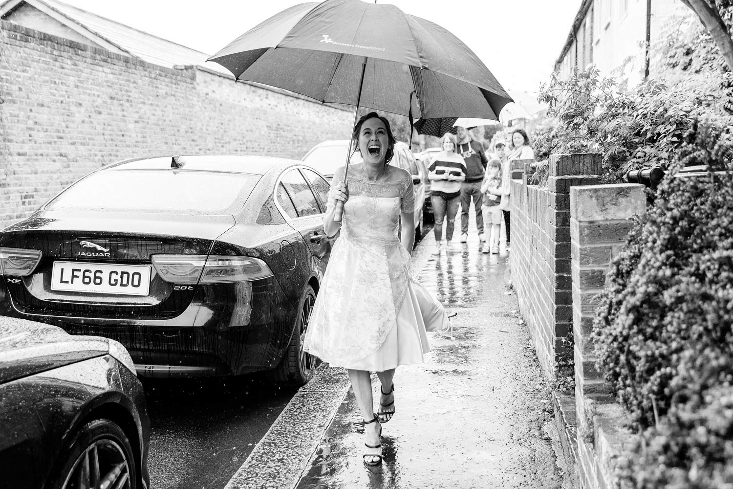 A bride laughs as she runs to the car in the rain.