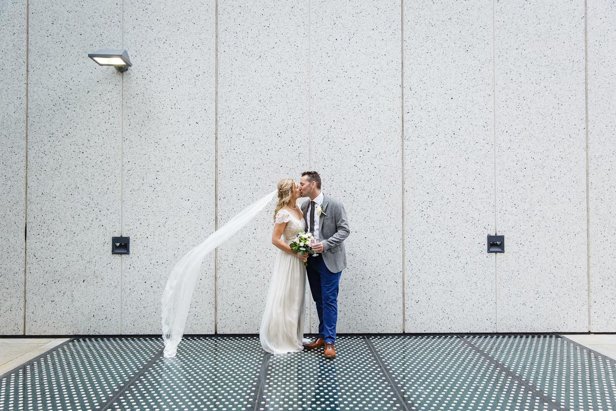 a couple pose for photographs outside The Brewery in Moorgate - London wedding photographer.