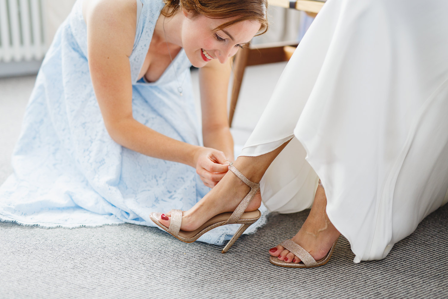 A bridesmaid puts on the bride's weddig shoes at The Laslett Hotel in London - wedding photographer