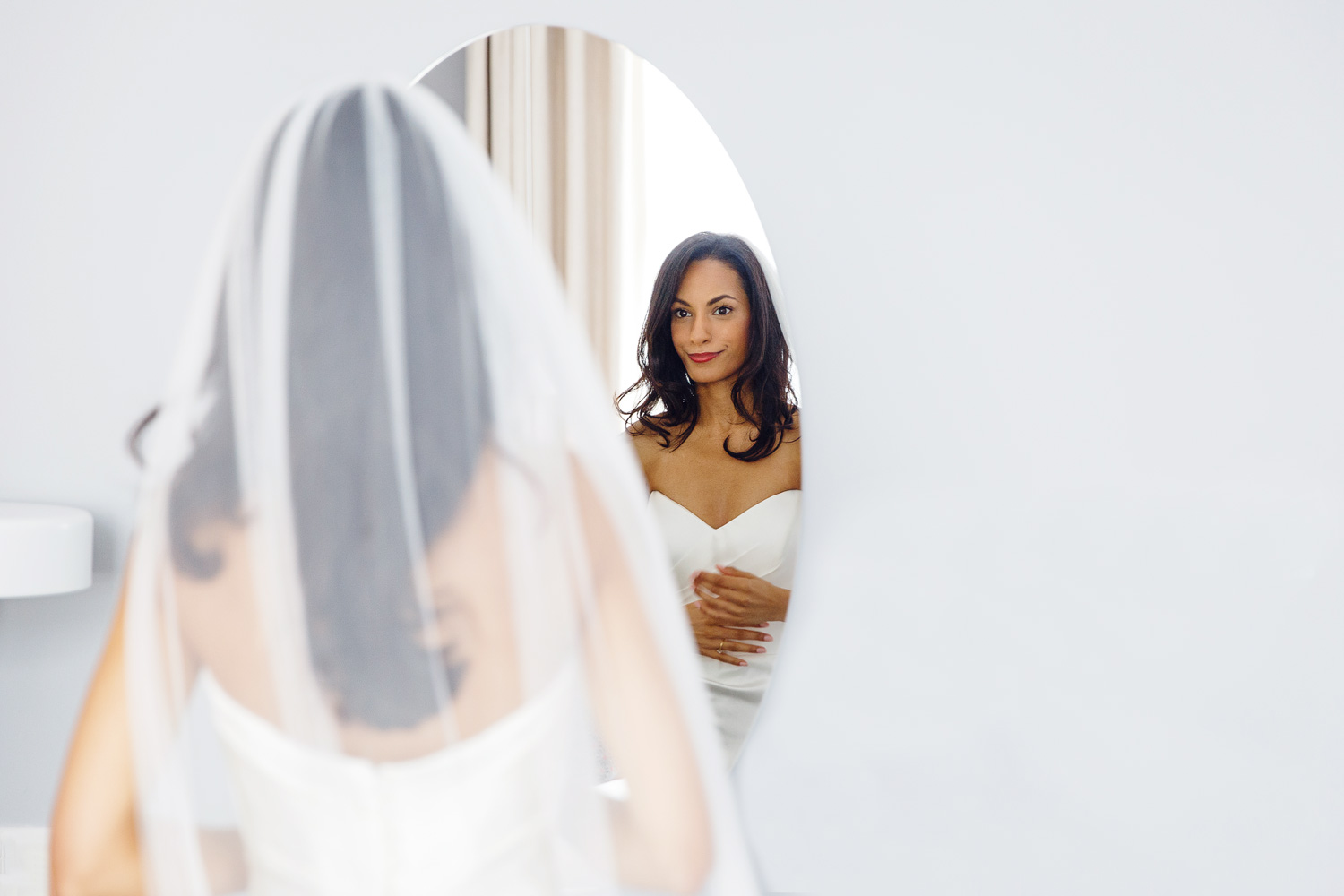 A bride looks in the mirror at The Laslett Hotel in London - wedding photographer