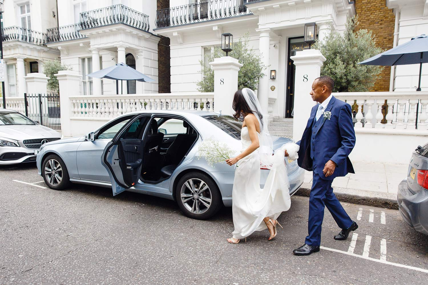 A bride gets into the bridal car with her father at The Laslett Hotel in London - wedding photographer