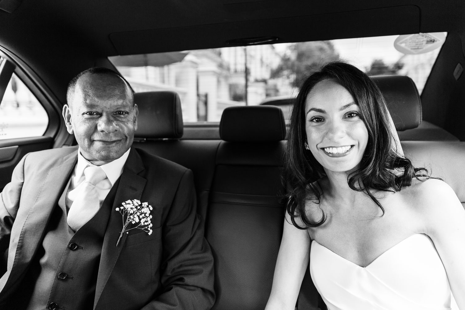 A bride smiles in the bridal car with her father at The Laslett Hotel in London - wedding photographer