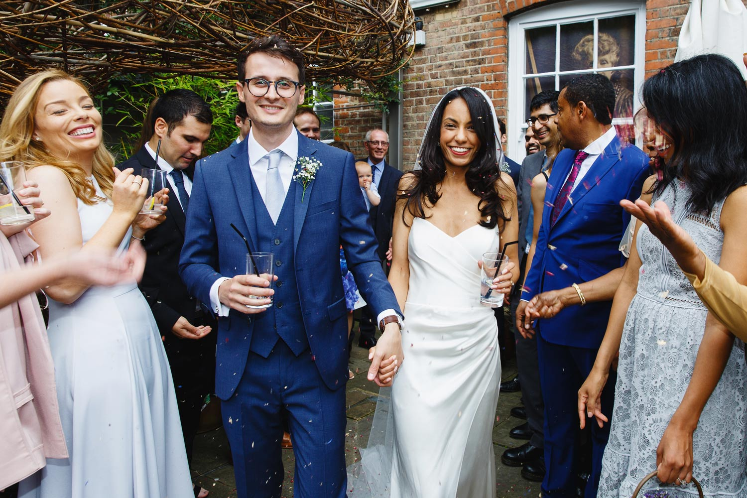 A couple walk through confetti at Burgh House Museum in Hampstead, London - wedding photographer
