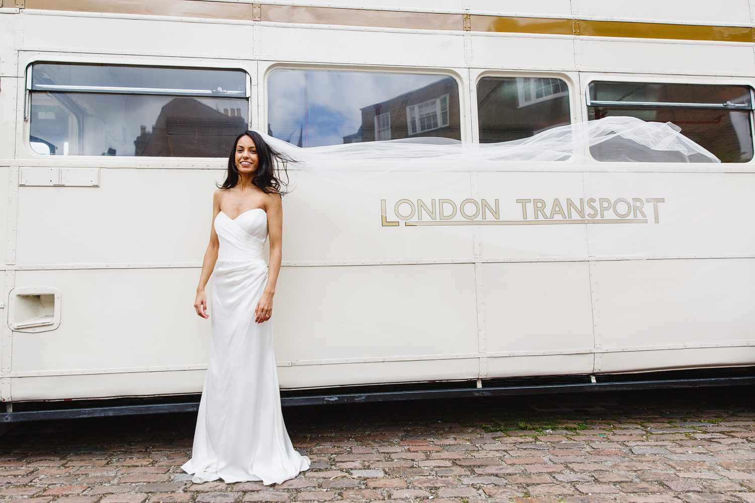 A bride stands in front of a white wedding bus at Burgh House Museum in Hampstead, London - wedding photographer
