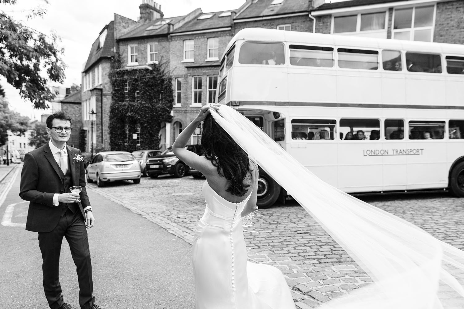 A bride and groom stand near their white wedding bus at Burgh House Museum in Hampstead, London - wedding photographer