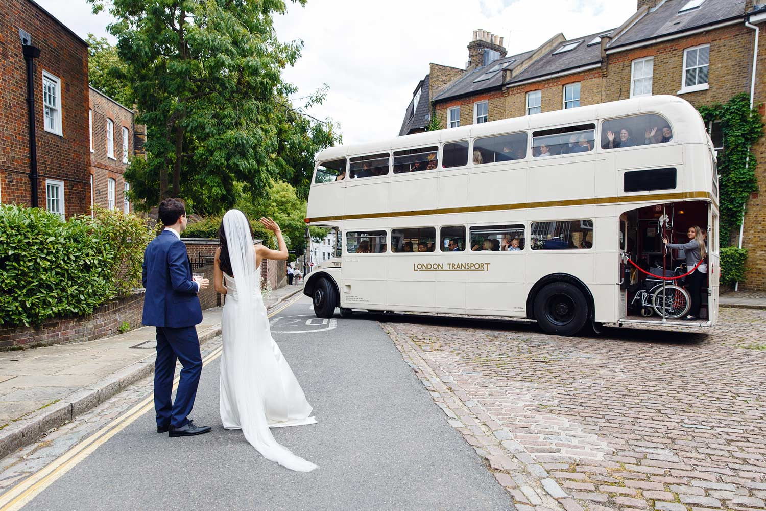 A couple wave goodbye to their guests at Burgh House Museum in Hampstead, London - wedding photographer