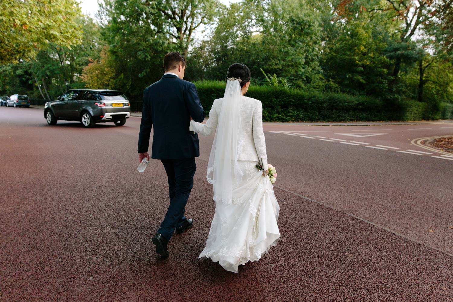 A newly married couple walk to the Langham Hotel for their wedding reception.